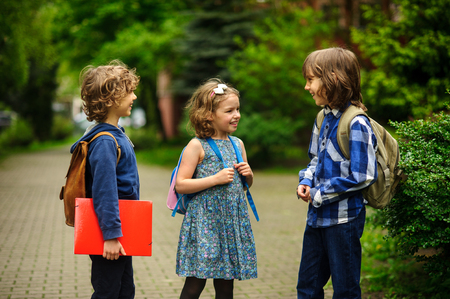 Cute little school students briskly talk on the schoolyard. Children have a good mood. Warm spring morning. Behind shoulders at schoolmates schoolbags. In hands of one of boys bright red folder. Stock Photo