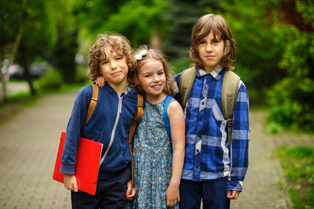 Three little school students, two boys and the girl, stand in an embrace on the schoolyard. Childrens friendship. Stock Photo
