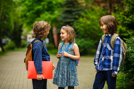 Little school students briskly talk on the schoolyard. Children have a good mood. Warm spring morning. Behind shoulders at schoolmates schoolbags. In hands of one of boys bright red folder.