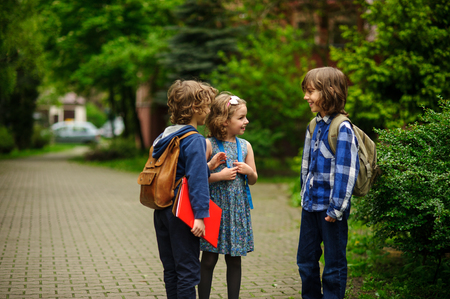 Little school students briskly talk on the schoolyard. Children have a good mood. Warm spring morning. Behind shoulders at schoolmates schoolbags. Reklamní fotografie