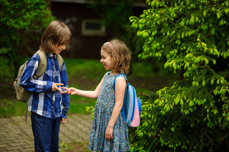 Two little school students, the boy and the girl, cheerfully communicate on the schoolyard. Behind shoulders at friends schoolbags. Against the background of magnificent spring greens. Stock Photo