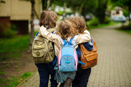 Three little school students go in an embrace to school. Childrens friendship.