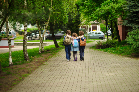 Three little school students, two boys and the girl, go in an embrace to school. Childrens friendship. Serene spring day. View from a back.