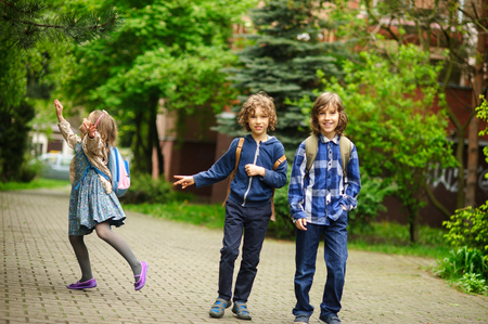 Three little friends hurry on lessons in school. The schoolgirl has noticed something on a tree. Boys smile. Stock Photo