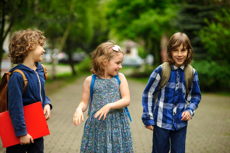 Little school students have started a game on the schoolyard. Two boys and the girl have fun waiting for the beginning of occupations. Fine morning. Stock Photo