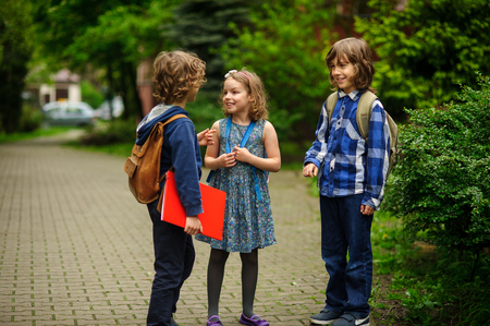 Little school students briskly and cheerfully talk on the schoolyard. Two boys and the girl have fun waiting for the beginning of occupations. Fine morning. Stock Photo