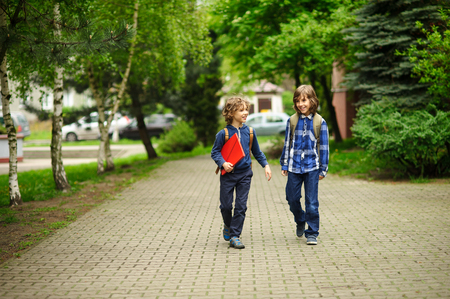 小学生は学校へ急ぎましょう。後ろのバックパックと男子生徒は、レッスンに行きます。友人は、良い気分を持ちます。彼らは活発に話します。
