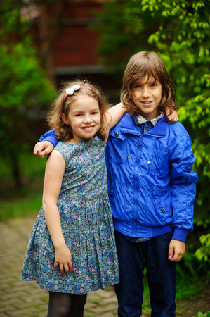 Two little friends, the boy and the girl, stand having embraced. Children smile. Stock Photo