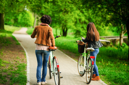 Two young women ride bikes in the spring park. Pleasure by nature and movements. Healthy lifestyle.