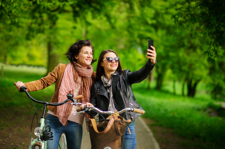Two nice young women make selfies during bicycle walk in the park. Fine weather. Girlfriends have an excellent mood. They smile.