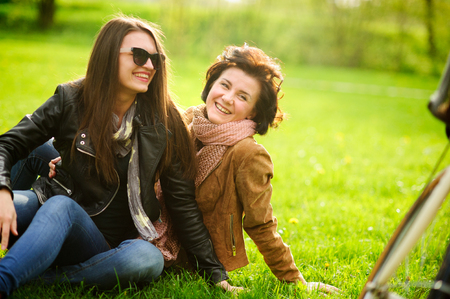 Two pretty young women cheerfully spend time in the spring park. Girlfriends frolicking while sitting on the green grass. Sunny warm day. Good mood.