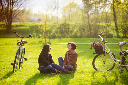 Charming young women sit on a green lawn in the spring park. Their bicycles stand nearby. Girlfriends with enthusiasm about something talk. Fine spring day.