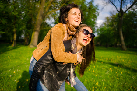 Two cute young women cheerfully spend time in the spring park. Women have a playful mood. Warm sunny day. Girlfriends enjoy the nature and communication. Stock Photo