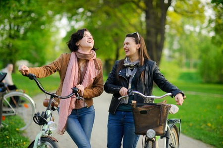 Two charming young women on bicycle walk in the spring park. Girlfriends have stopped and talk. Against the background of fresh spring greens
