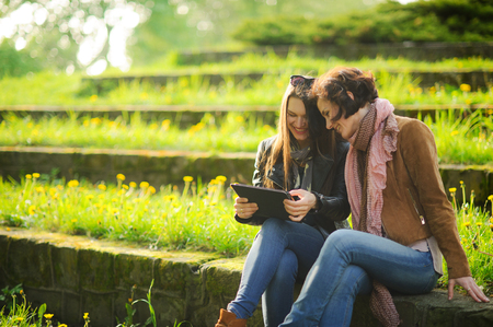 Young women sit at stone steps with the tablet in hands. Girlfriends with interest look at the screen. Pleasant outdoor recreation in spring day. Young green grass and yellow dandelions. Stock Photo