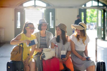 駅で陽気な女の子。陽気な残りの期待の若い観光客。活発ガール フレンドを話します。パスポートと航空券の女の子の手。夏休み。