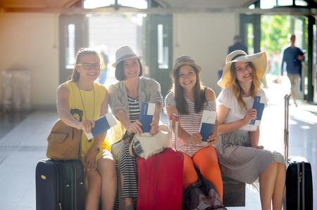 Charmante toeristen verheugen zich over het begin van een reis. Meisjes zitten op het station. Ze tonen vreugdevol de paspoorten en tickets. Zomervakantie. Anticiperen op vrolijke rust.