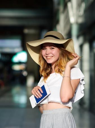 パスポートとチケット、手につば広の帽子でかわいい女の子。ポーズの女の子。鉄道駅。夏の休日。 写真素材