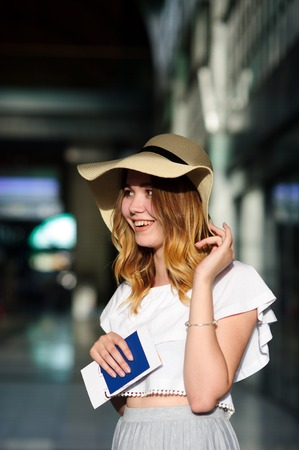 the furlough: Pretty girl in a wide-brimmed hat with the passport and tickets in a hand. Girl posing. Railway station. Summer holiday. Stock Photo