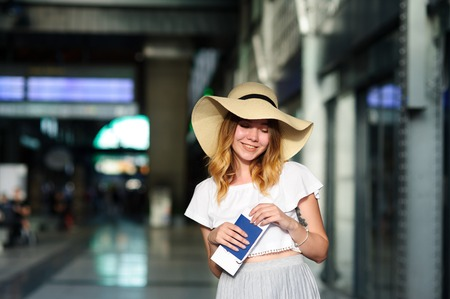 Pretty girl in a wide-brimmed hat with the passport and tickets in a hand. Girl posing. Railway station. Summer holiday. Stock Photo