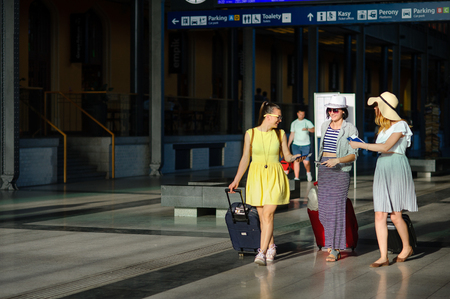 Young women hurry to their train. They roll their suitcases. The tourists are in a good mood. Summer vacation. Stock Photo