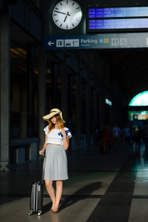 Charming girl in sun-hat in the waiting room of the train station. Nearby is a suitcase. In hand her passport and tickets. Time of summer holidays.