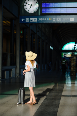 Girl in a sun-hat in the waiting room of the railway station. The tourist is study the train schedule. Time of summer holidays. Stock Photo