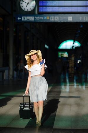 Cute girl in sun-hat in the waiting room of the train station. Tourist with a suitcase in a hurry for her train. Time of summer holidays.