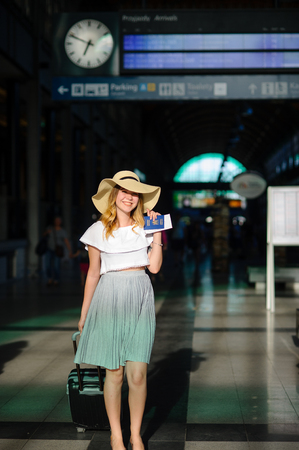 the furlough: Charming girl in sun-hat in the waiting room of the train station. Nearby is a suitcase. In hand her passport and tickets. Time of summer holidays.