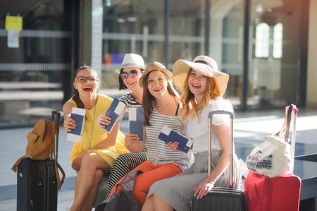 魅力的な観光客は旅行の初めに喜ぶ。駅で女の子が座っています。パスポートと航空券を見せる嬉しそう。夏休み。陽気な残りの予想。