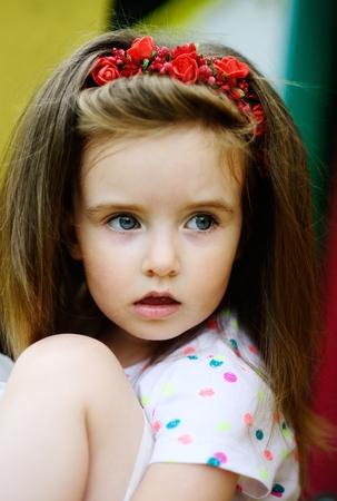 Portret van het charmante meisje van 4-5 jaar. Mooi lang blond haar. Een krans van rode kleuren op het hoofd. Expressieve grijsblauwe ogen. Heldere lippen.