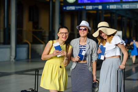 the furlough: Three cute young women at the train station. They have passports and tickets in their hands. Girlfriends are happy at the beginning of an exciting journey. Time of summer vacation.