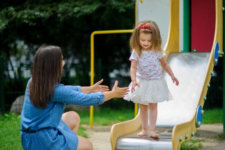 Mom and her little daughter are playing on the playground. Barefooted baby stands on the edge of the slide. Mom stretches out her hands to the girl. Stock Photo