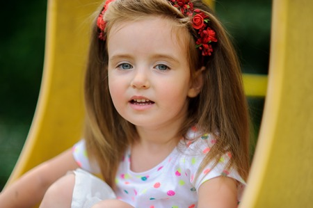 likeable: Portrait of the charming girl of 4-5 years. Beautiful long fair hair. A wreath from red colors on the head. Expressive gray-blue eyes. Bright lips. Stock Photo