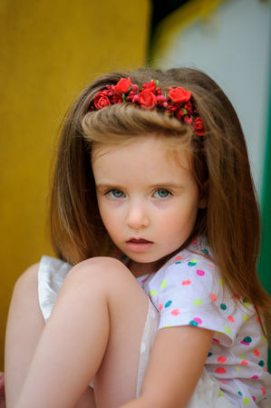 Portrait of the charming girl of 4-5 years. Beautiful long fair hair. A wreath from red colors on the head. Expressive gray-blue eyes. Bright lips. Stock Photo