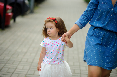 Young mother walks in the park with the little daughter. The woman holds the charming five-year-old girl by a hand.