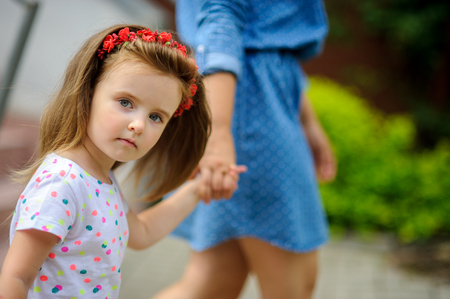 likeable: Young mother walks in the park with the little daughter. The woman holds the charming five-year-old girl by a hand.