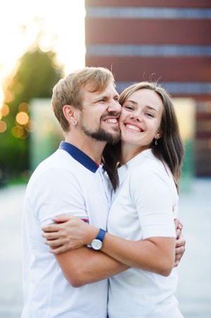 Portrait of beautiful young couple. Young people sit having nestled to each other, cheek to cheek. They happily smile. Stock Photo