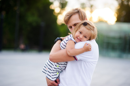 Young father holds the little daughter on hands. Man gently presses to himself the child. Baby put her head on her fathers shoulder. Stock Photo