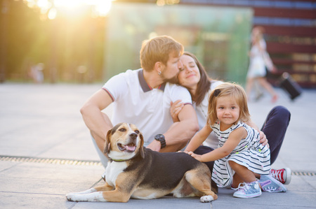 Wonderful young family is resting sitting on the ground. Dad, Mom, little daughter and beagle. Warm summer weather, good mood.