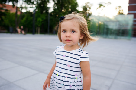 Portrait of a two year old girl in a striped dress. Nice face, short blond hair, serious look. Stock Photo