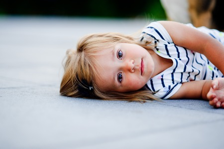 Portrait of a two year old girl in a striped dress. Nice face, short blond hair, serious look. Cute baby lies on the ground and looks curiously at the camera. Stock Photo