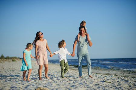 Big happy family walking at the beach. Mom, dad and three children. The blue sky, the sun, fresh sea wind. Pleasure from nature and communication. Stok Fotoğraf