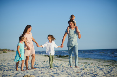 Big happy family walking at the beach. Mom, dad and three children. The blue sky, the sun, fresh sea wind. Pleasure from nature and communication. Stock Photo