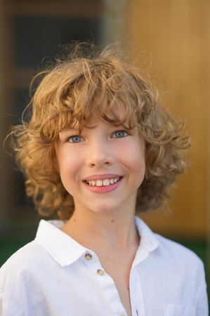 Portrait of the nice boy of 10-11 years. The fellow has beautiful fair curly hair, blue cheerful eyes, suntanned skin, a pleasant smile. The boy is dressed in a white shirt. Stock fotó
