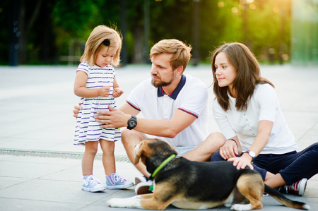 Young family spending a day off in the city park. The husband and wife are sitting on the ground. Next to them is a small adorable daughter and a pet - beagle. Warm summer day. Good mood.