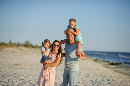 Young happy family on the beach. A woman is holding a younger daughter in her arms. The second girl sits on her fathers shoulders. Joy of communication with children and nature.
