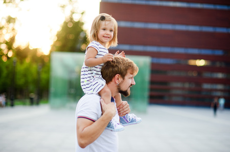 Young man holds his small daughter on his shoulders.