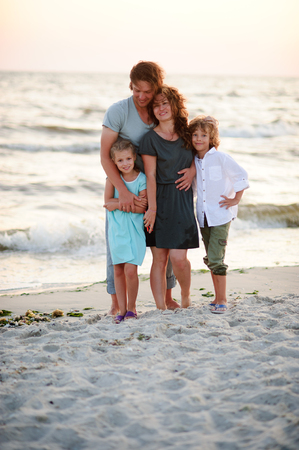 stroll: United family of four against the background of sea waves.