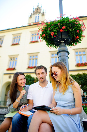 windows: Three students are preparing for exams. Two girls and a guy sitting on a bench and talking animatedly. In the hands of their notes and their tablet.